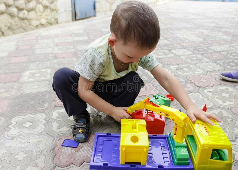 Beautiful little boy playing with a toy garbage truck stock image