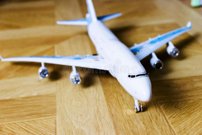 Model of passenger plane on wooden background. Pictured in the photo model of passenger plane on wooden background, the front of the back focus is out of focus royalty free stock photo
