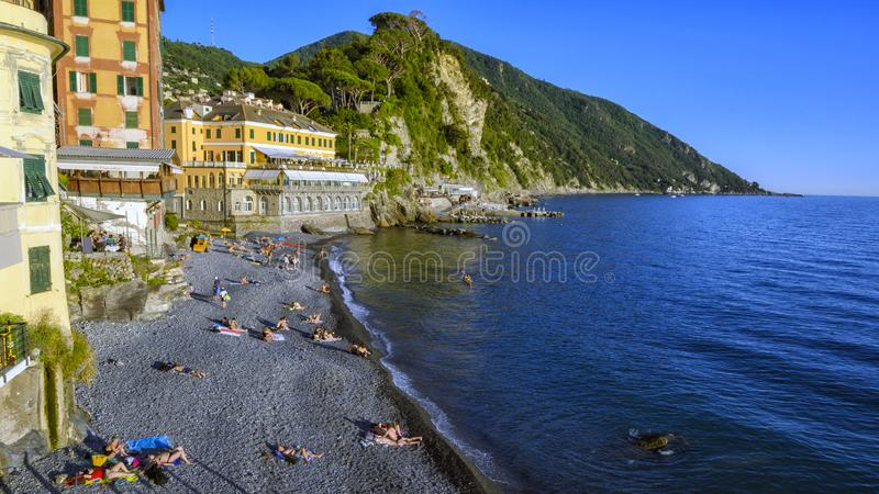 Rocky beach with tourists and painted houses, Camogli, Northern Italy stock photography