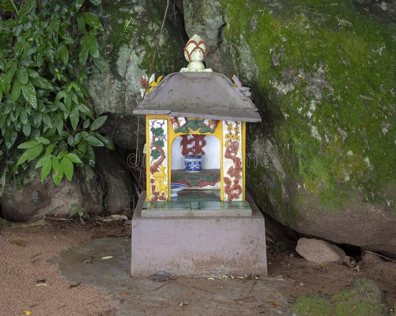 Small roadside Buddhist shrine, Vendana Lagoon, Vietnam. Pictured is a small roadside Buddhist shrine near Vendana Lagoon, Vietnam. The small blue and white royalty free illustration