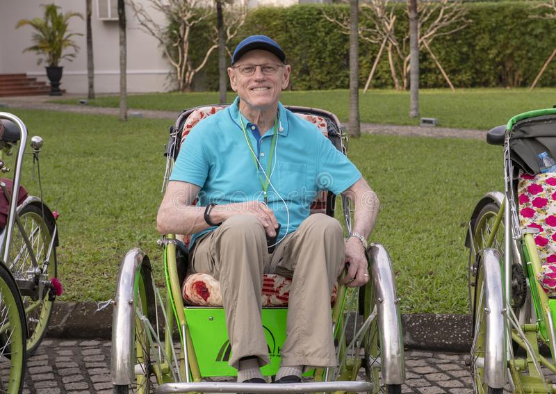 Elderly male tourist ready for a cyclo tour in Vietnam royalty free stock photos
