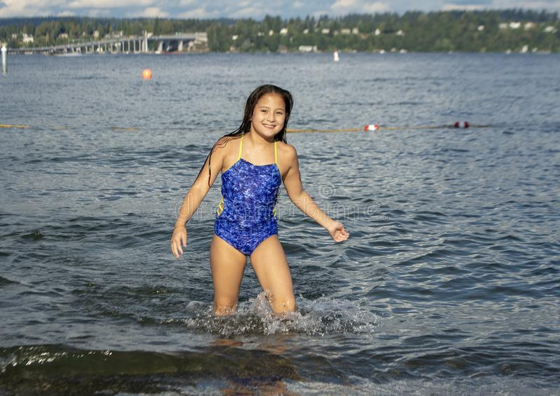 Ten year old Amerasian girl having fun in the lake at Greenlake Park, Seattle, Washington. Pictured is a smiling ten yearold Amerasian girl having fun on stock photography