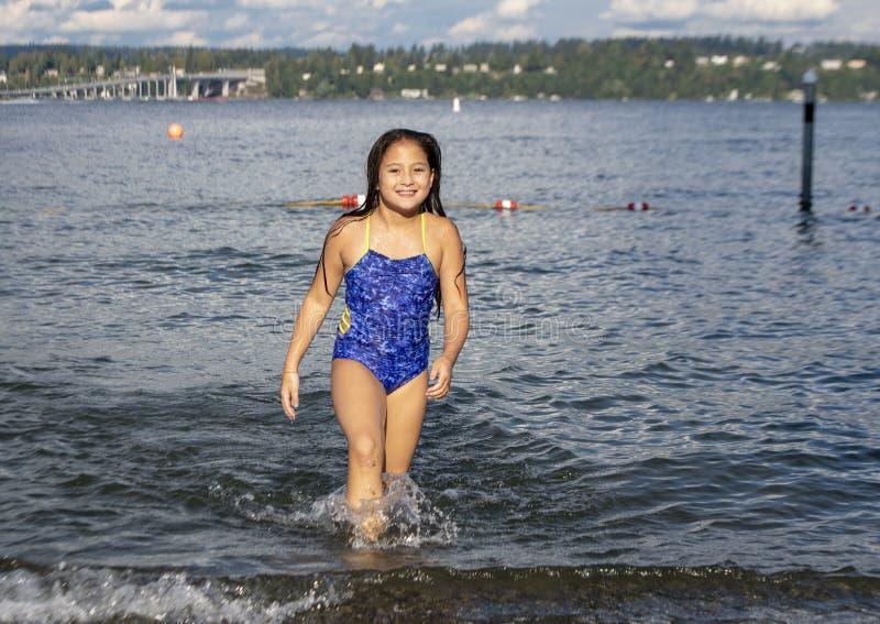 Ten year old Amerasian girl having fun in the lake at Greenlake Park, Seattle, Washington. Pictured is a smiling ten yearold Amerasian girl having fun on stock photos