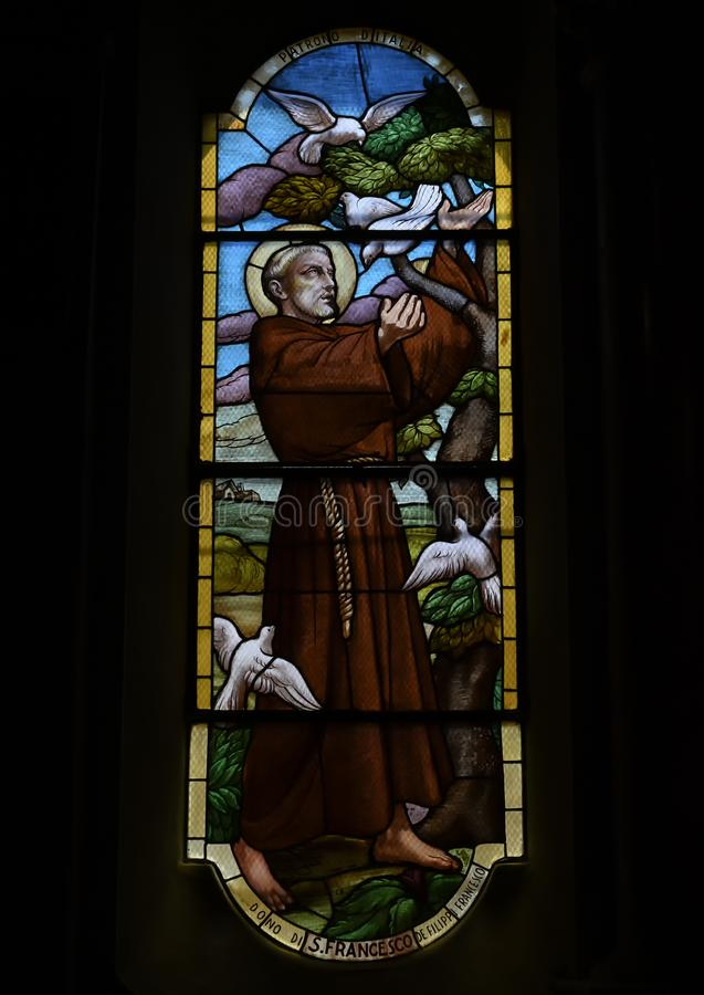 Stained glass of Saint Francis taming the white doves, Church of Saint Martin, Portofino, Italy. Pictured is a stained glass of Saint Francis taming the white stock photos