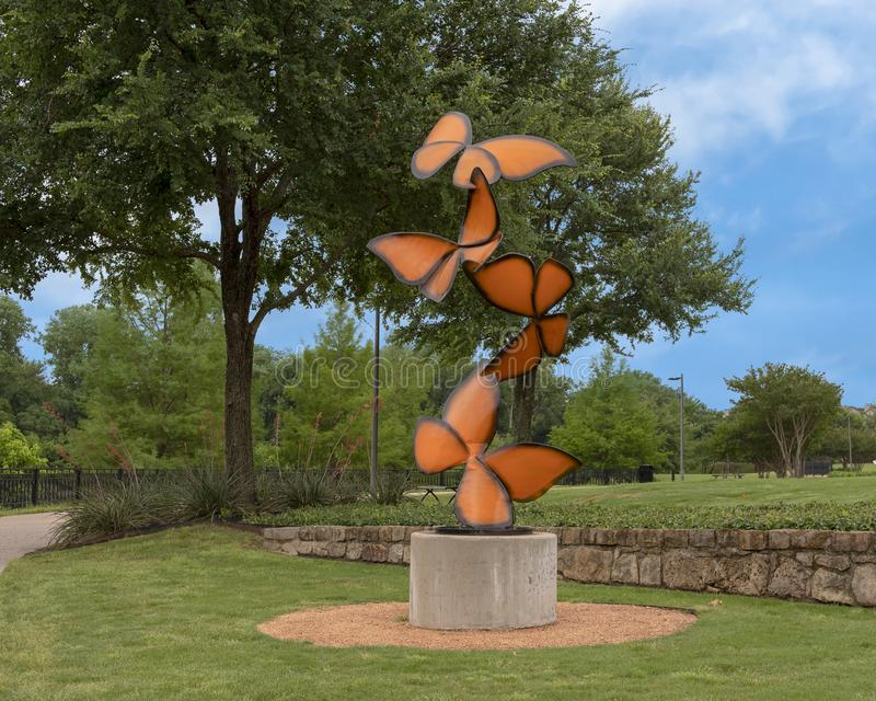 `Life Flutters By`, a steel sculpture by Laura Walters Abrams located in Watercrest Park, Dallas, Texas. Pictured is a steel alloy with powdered paint sculpture royalty free stock photo