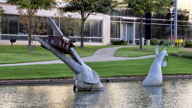 Giant fish eating a house by Joe Barrington, Hall Park, Frisco, Texas. Pictured is a steel sculpture by Joe Barrington of a giant fish eating a house in a pond stock image