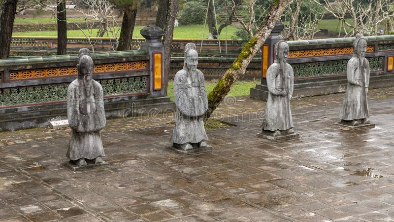 Stone mandarin sculptures in the forecort preceding the Stele Pavilion in Tu Duc Royal Tomb, Hue, Vietnam. Pictured are stone mandarin sculptures in the stock photos