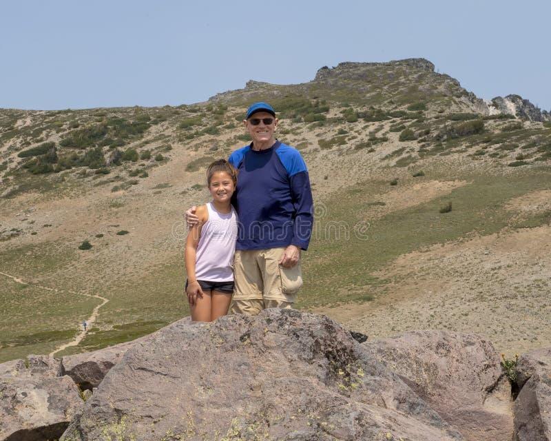 Ten year-old Amerasian girl and grandfather having fun in Mount Rainier National Park, Washington stock images