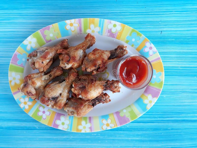 Pictured top view, fried chicken leg with herbs in a dish with tomato sauce stock photo