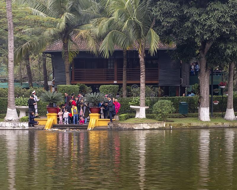 Tourists feeding carp with the Stilt House of Ho Chi Minh in the background, Hanoi, Vietnam royalty free stock photo