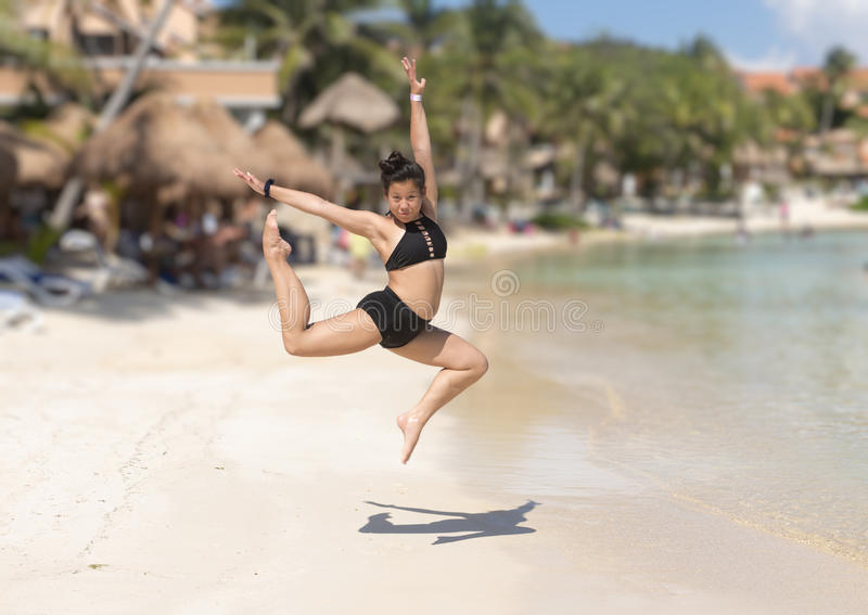 Athletic Amerasian girl dancing on the beach. Pictured is a twelve-year-old Amerasian girl in a black two-piece bathing suit flying in a perfectly posed athletic royalty free stock images
