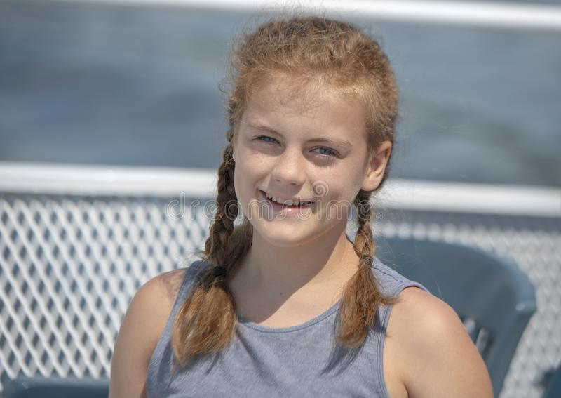 Twelve year-old caucasian redheaded girl with pigtails enjoying a vacation tour boat ride on Elliott Bay in Seattle, Washington. stock photos