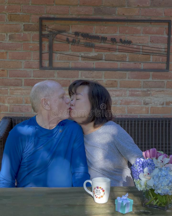 Old love birds on Mother`s Day, an appreciative kiss for gifts given. Pictured are two old married love birds on Mother`s Day.  The husband is receiving an royalty free stock images