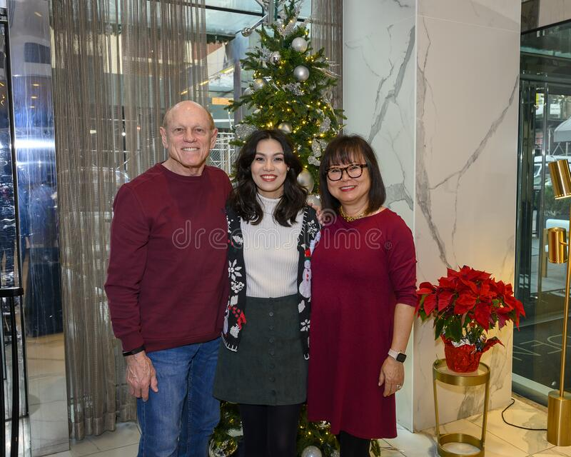 Caucasian father, Korean mother and Amerasian daughter posing before a tree on Christmas morning in New York City stock images
