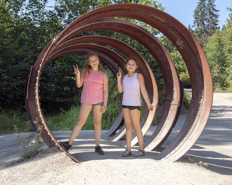 Cousins posing in the whale bone sculpture, Snoqualmie Park, State of Washington. Pictured are an 11 year-old Caucasian girl and her 10 year-old Amerasian cousin stock images