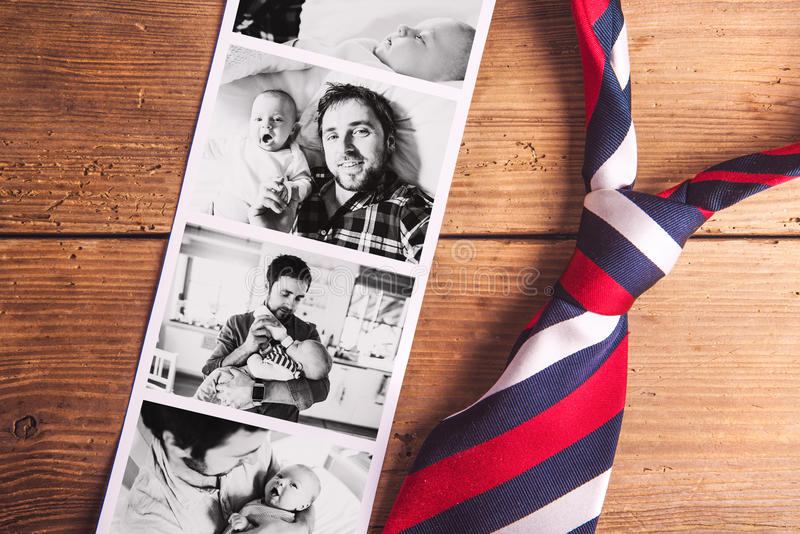 Pictures of father and baby son. Fathers day. Studio shot. Colorful tie and various pictures of young father and his cute newborn baby son. Fathers day concept royalty free stock photo