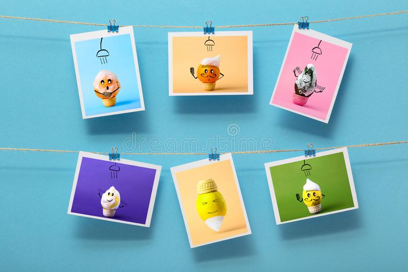 Pictures with funny washing fruits hanging on a linen thread on stationery clips on a colored background, concept of cheerful mood stock image