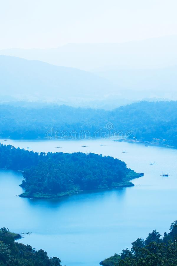 Picturesque aerial view of the blue lake in a mountain range. Picturesque aerial view of the Sirikit lake in a mountain range in blue fog, local fisherman with royalty free stock images