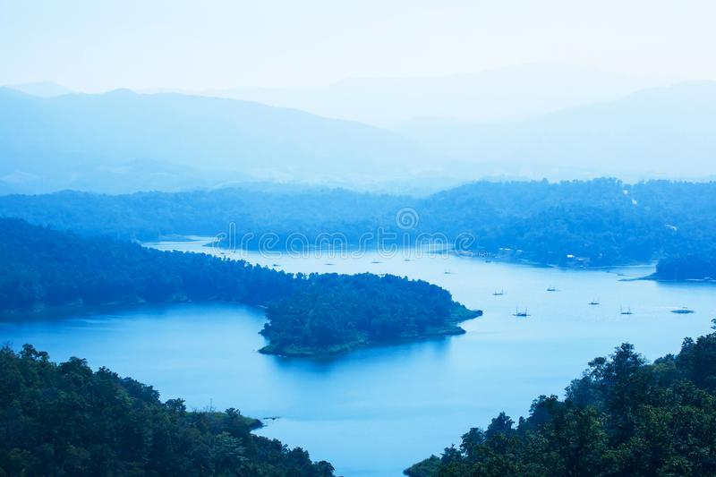 Picturesque aerial view of the blue lake in a mountain range. Picturesque aerial view of the Sirikit lake in a mountain range in blue fog, local fisherman with stock photography