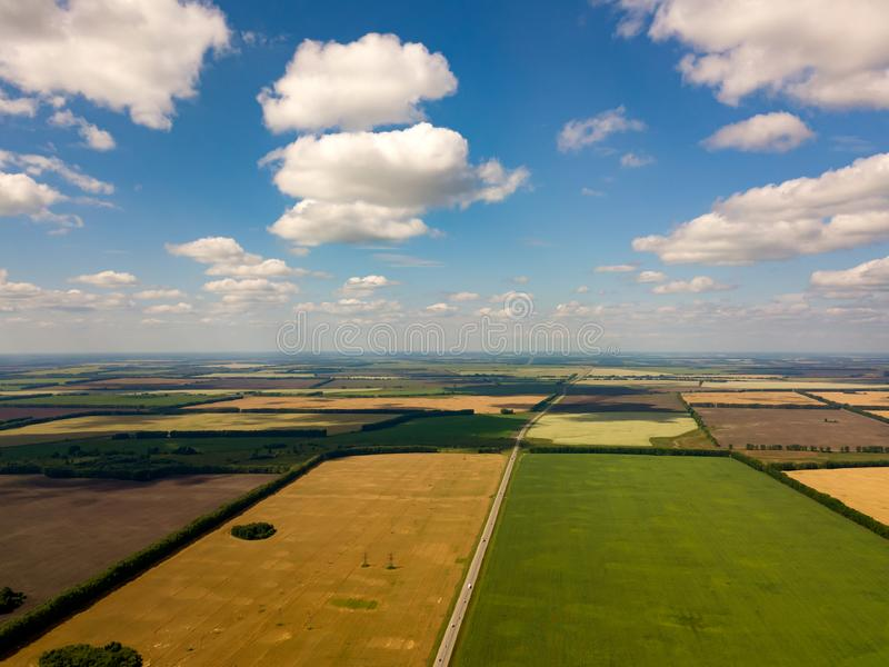 Picturesque aerial view of farmland in the countryside, blue sky with white clouds, colorful fields with different planted crops,. Green grass and lake trees stock images