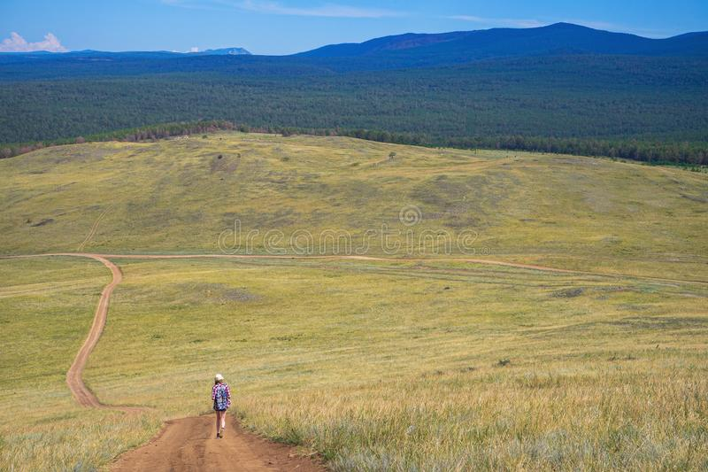 Picturesque amazing landscape of steppe, forest and mountains with small figure of young tourist girl walking away country road royalty free stock photography
