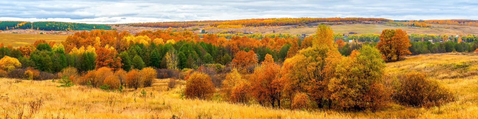 Picturesque autumn landscape in green and yellow colors. Panoramic view from hill to lowland with grove, village and field in stock photos