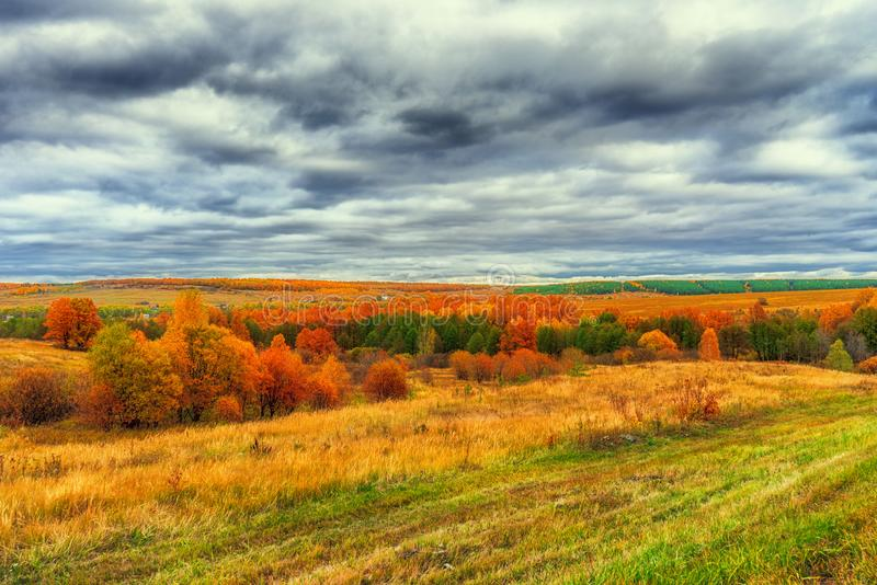 Picturesque autumn landscape in green and yellow colors. Panoramic view from hill to lowland with grove, village and field in stock photo