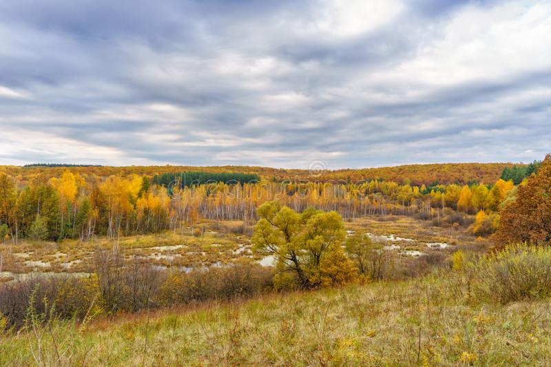 Picturesque autumn landscape. View from the hill to the lowland with forest and swamps. Beautiful natural background stock images