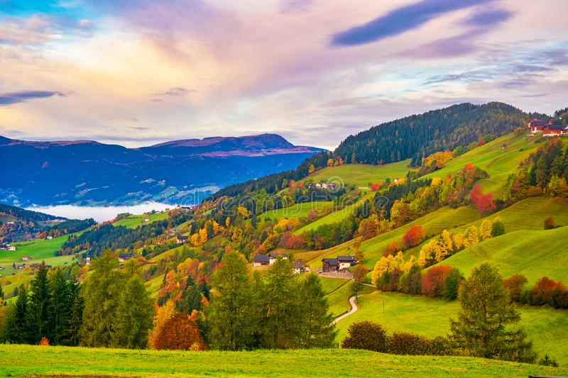 Picturesque autumn scenery with meadows, foliage trees and mountain hills under colorful clouds stock image