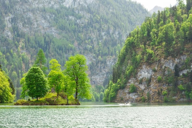 Picturesque bavarian lake, koenigssee, bavaria, germany. The landscape of a mountain lake with a small island in the middle. Picturesque bavarian lake stock image