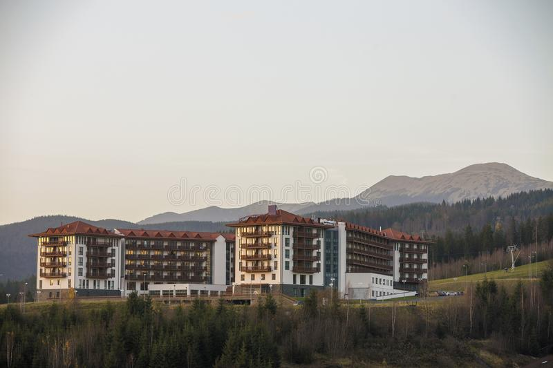 Picturesque big luxury hotel complex exterior, tourist accommodation with modern architecture on green spruce mountain ridge and stock image