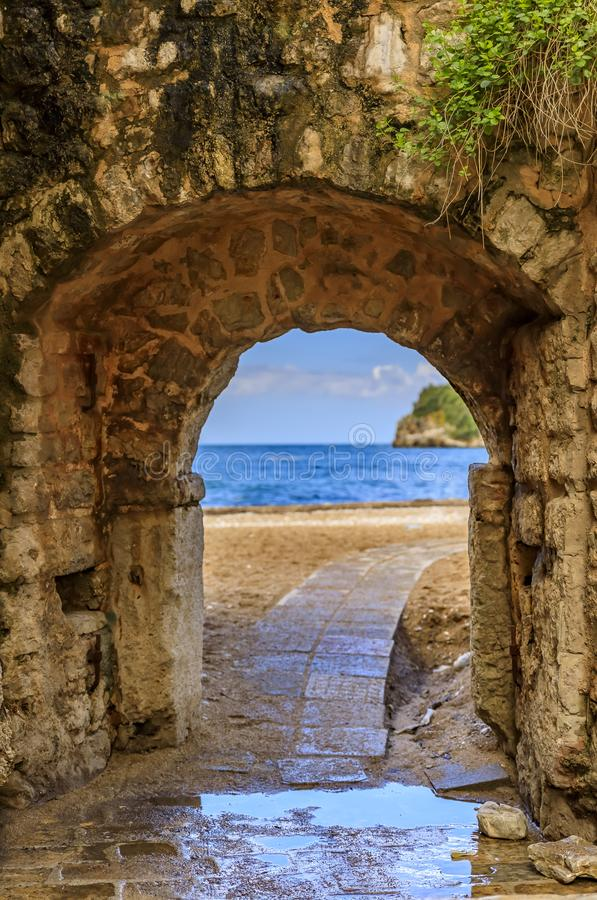 Picturesque brick arch and path of the medieval Old town open onto the Adriatic Sea in the Balkans in Budva, Montenegro. Picturesque brick arch and cobbled path stock images