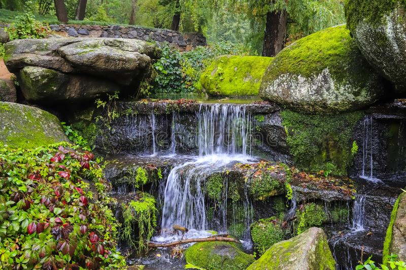 A picturesque cascade waterfall among large moss covered stones in the landscape Sophia Park, Uman, Ukraine, Autumn royalty free stock images
