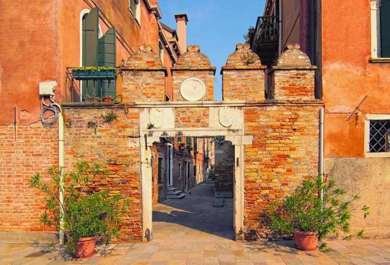 Picturesque city landscape of Venice. Medieval facade of red brick building and gate door. Non-tourist part of the city royalty free stock photography