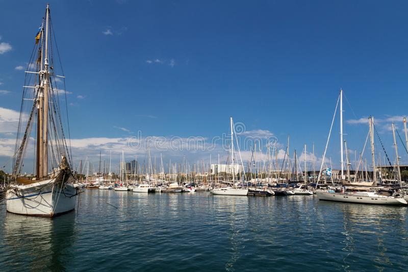 Picturesque city port in Barcelona. Famous Port Vell. Beautiful white yachts and sailboats on blue sky background stock image