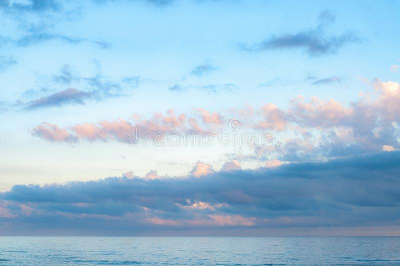 Picturesque cloudscape above calm sea water. In violet dusk evening with blue and lilac fluffy clouds in clear light blue sky. Seascape of Black sea. Summer royalty free stock images
