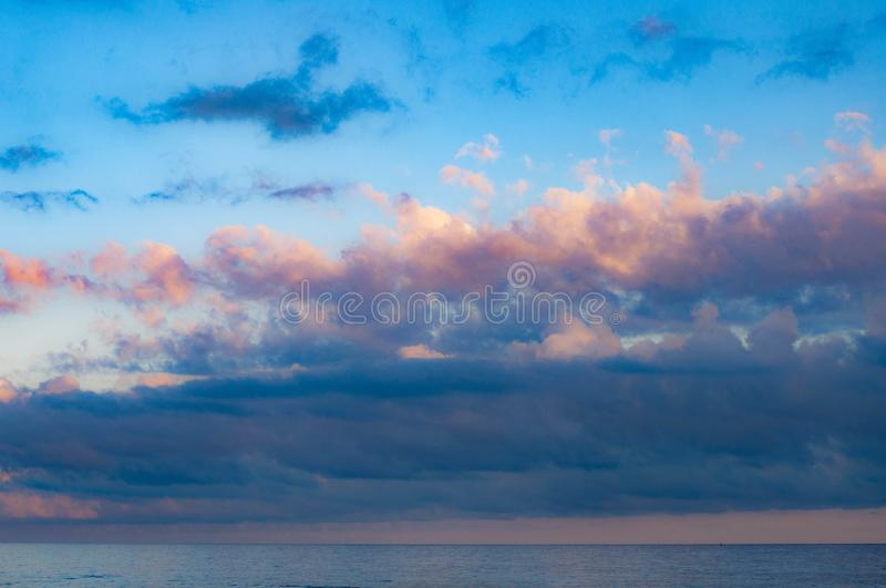 Picturesque cloudscape above calm sea water. In violet dusk evening with blue and lilac fluffy clouds in clear light blue sky. Seascape of Black sea. Summer stock photo