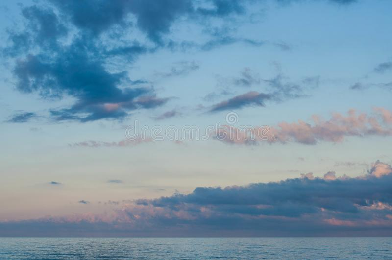 Picturesque cloudscape above sunset calm sea. In violet dusk evening with blue and lilac clouds in clear light blue sky with touch of pink. Seascape of Black royalty free stock photos