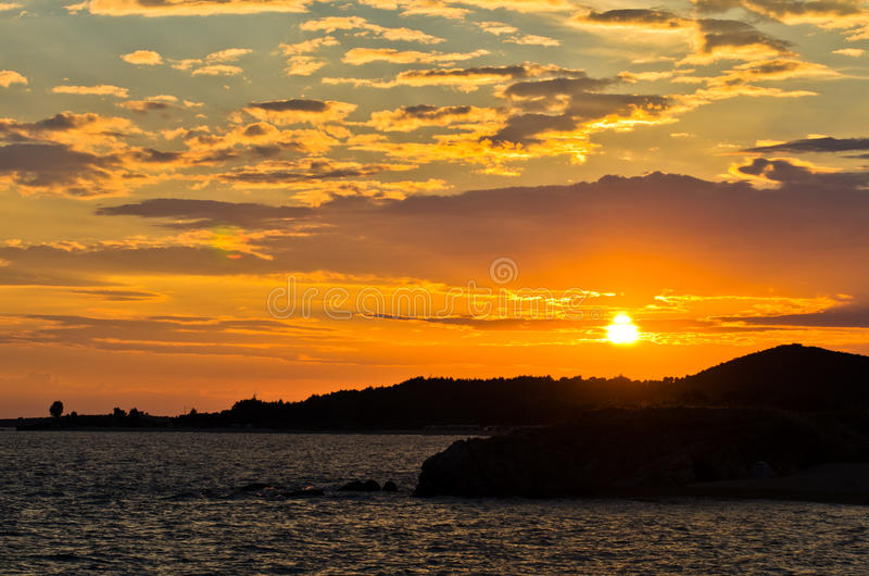 Picturesque cloudscape with silhouette of a sea rocks at sunset. West coast of peninsula Sithonia, Greece stock image