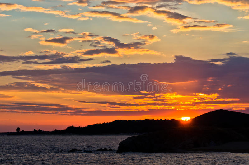 Picturesque cloudscape with silhouette of a sea rocks at sunset. West coast of peninsula Sithonia, Greece royalty free stock images