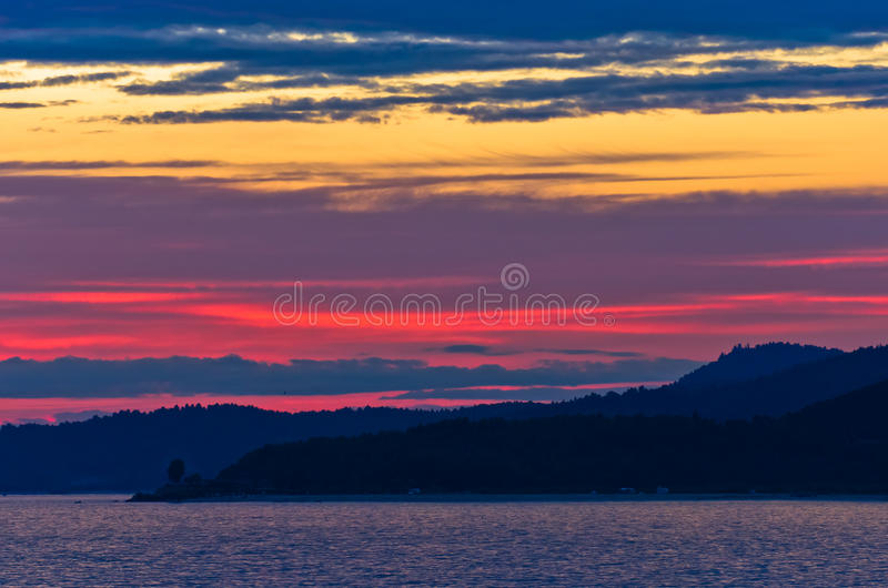 Picturesque cloudscape with silhouette of a sea rocks at sunset. West coast of peninsula Sithonia, Greece stock photo