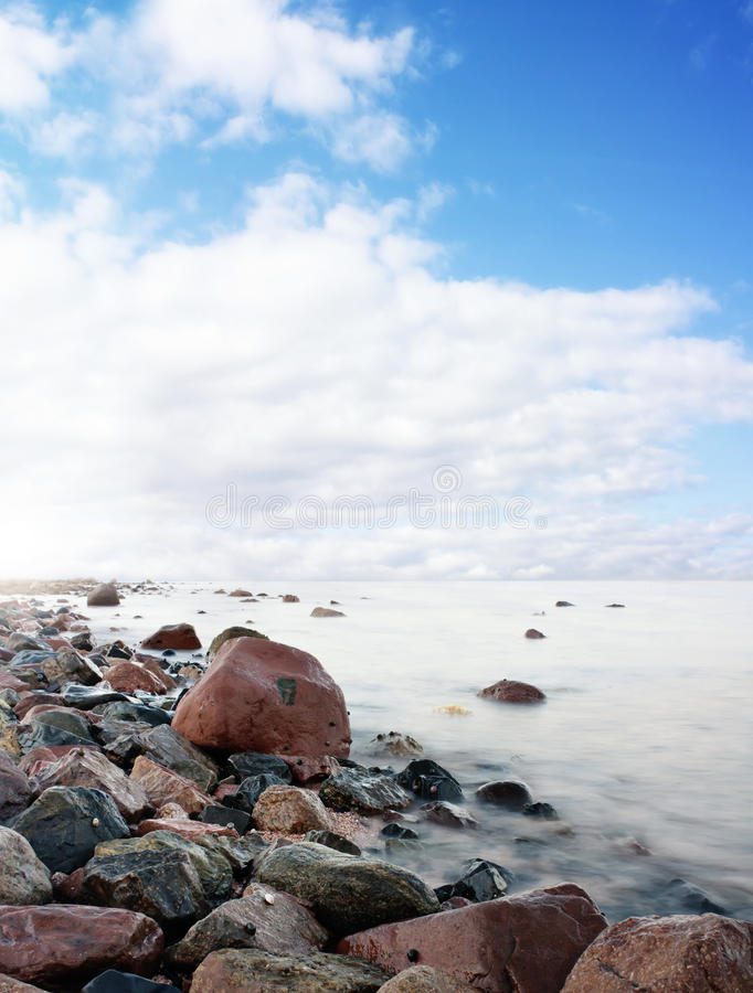 Picturesque coastline. Scenic view of rocks and boulders on picturesque coastline with blue sky and cloudscape background royalty free stock photo