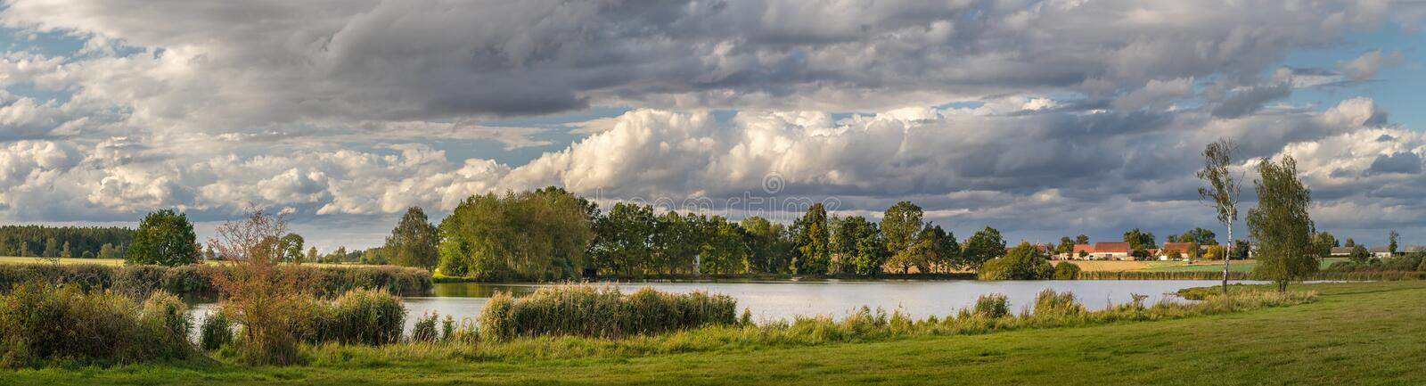 Picturesque country landscape with pond, meadow and trees royalty free stock photo