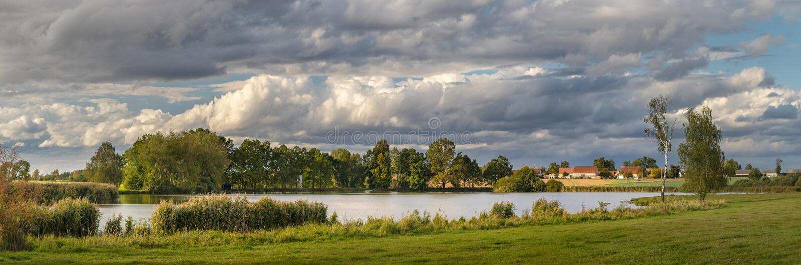 Picturesque country landscape with pond, meadow and trees stock images