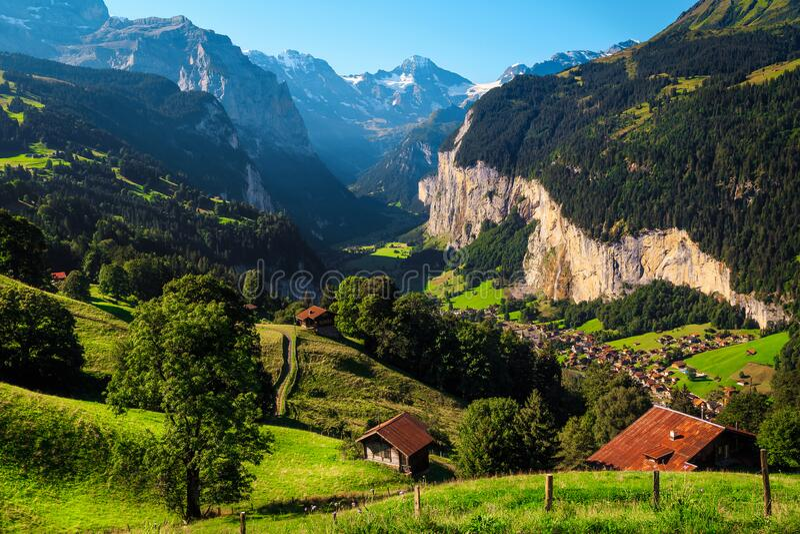 Picturesque green fields and snowy Mountains, Wengen resort, Lauterbrunnen, Schweiz arkivfoto