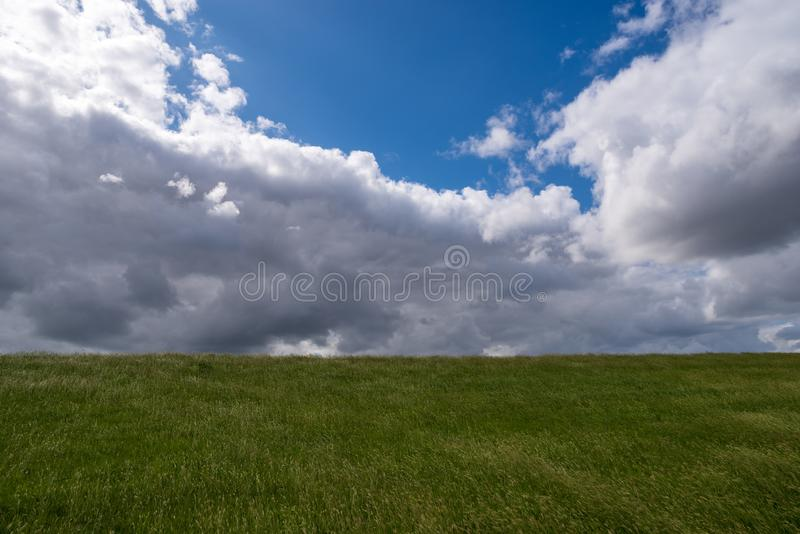 Picturesque green meadow with blue sky and dramatic clouds. Plain landscape. Germany royalty free stock image