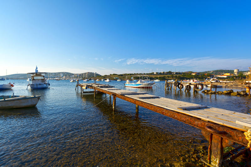 Picturesque harbor. View of an old rusty pier and old fishing boats at a picturesque harbor in Greece stock photo