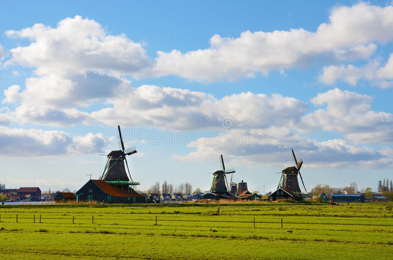 The picturesque landscape with aerial mill on the channel in Zaanse Schans, Holland on a background cloudy sky royalty free stock images