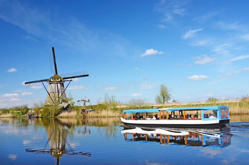 The picturesque landscape with aerial mills and boat on the channel in Kinderdiyk, Netherlands royalty free stock photos