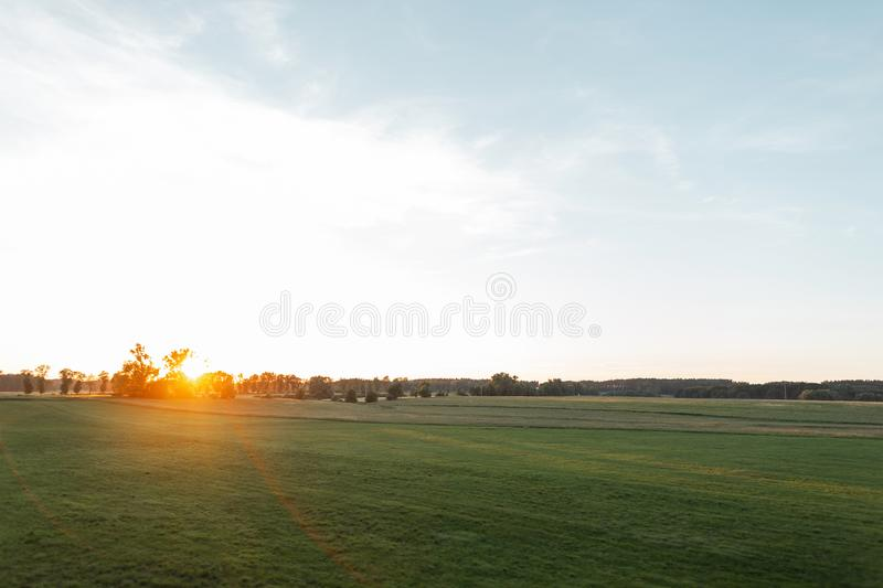 Picturesque landscape c blue sky with a bright orange sunset on the horizon. Field with green grass in summer warm day royalty free stock image